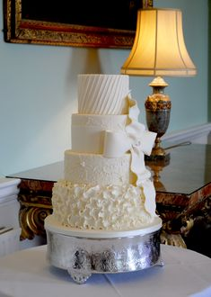 ivory wedding cake with petal ruffles and sugar bow
