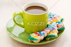 image of coffee cup and cookies. - Close-up image of green coffee cup with Christmas tree shaped cookies in green saucer.