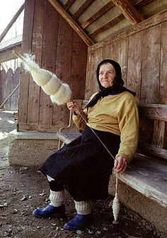 A Romanian woman spinning yarn with a distaff.