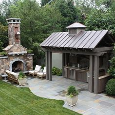 Outdoor kitchen with metal roof. Blue stone patio and huge exterior fireplace. Outdoor kitchen with