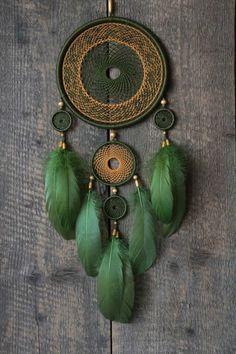 selbstgebastelter Traumfänger mit dunkelgrünen und orangen Fäden