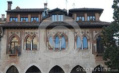 Photo made in the cathedral square in Treviso in the Veneto (Italy). The picture shows the facade, overlooking the cathedral, in a beautiful building built by the Venetians. They are particularly beautiful, and reveal the architectural style of the Venetian Republic, the seven windows (two mullioned windows and a three), placed above the arches with vaulted tip of the porch, and two small balconies.
