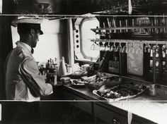 "Preparing lunch on the Imperial Airways aeroplane 'Scylla', 19 November 1936. Photograph by James Jarche showing the galley on the Imperial Airways aeroplane ""Scylla""."