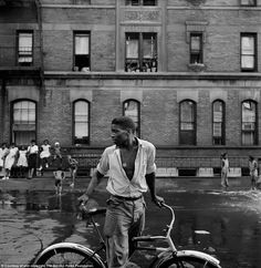 Struggle: This untitled photo, taken in Harlem, New York in 1948, shows a young African-American man cycling through a street where poor children wash with a hose