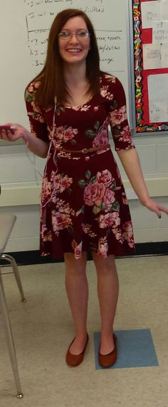 Outfit of the day is a red floral dress with a brown belt, and brown matching flats.