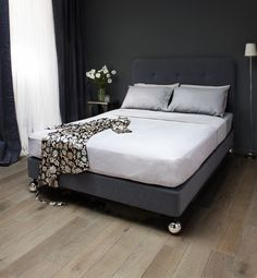 Bed no 3. Grey wool upholstered buttoned headboard and divan on polished nickel balls.