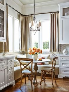 When it comes to eat-in kitchens, dining doesn't get much finer than this. French antique chairs pull up to a metal-top table with a striking pedestal base that also serves a plush banquette. The bench's shapely back, dual fabrics, and nailhead trim stack up for high-style seating. #traditionalkitchens