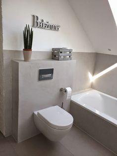 Graues Bad mit weißen Elementen.