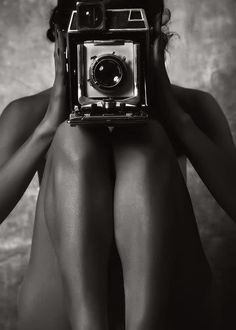 strategically nude model with vintage camera