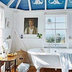 Painted Perfection    Exposed studs frame the painted datura flowers on the ceiling. The ocean blue hue makes a perfect backdrop for white accents such as the English antique tub. The small vanity adds a dainty quality to the space's whimsical mood.