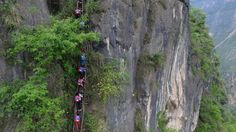 Chinese kids who climb 2,500-foot ladder may get stairs.  Children carry their school backpacks as they climb a cliff on their way home from school in Zhaojue county