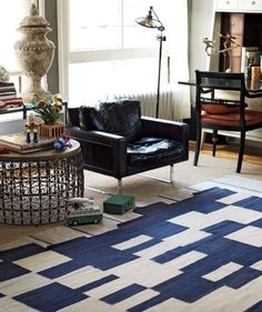 A bold pattern on the floor gives a focal point to a room with a mix of furniture styles—it's a unifier. To ease into the look, start with a neutral sisal, top it with a subtle stripe, then put the showiest rug on top. Worried about pattern overload? A solid (rather than glass) coffee table can mitigate the effect.
