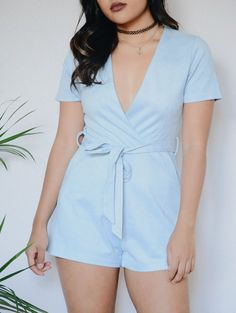 Short sleeve plunging neckline surplice front self belted romper.