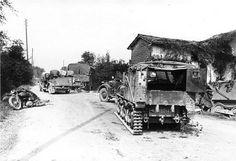 1940, France, Des véhicules allemands traversent un village dont les rues sont encombrées de véhicules français abandonnés