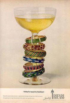 1968 - TRIFARI - ADS - Trifari's toast to fashion! - Exuisite jewel-toned enamel in sophisticated designs that go from little luncheons throughout big evenings. Bracelets $12,50 to $25. Earrings $5 to $15. Bangles around wine glass.
