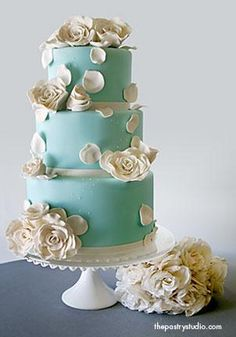 The Jackie  this design features a soft teal background with sugar-paste garden roses and rose petals. each tier is anchored with an ivory ribbon.
