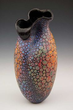 This vase has no defined shape, making it look more abstract. The colors and circle patterns also add to that theme