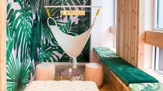 Inside James Morrissey's New Bar The VNYL: palm tree wall paper and bench with a white hammock and couch | coveteur.com