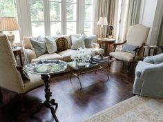 A wall of windows floods this formal living room in natural light. Lightly patterned chairs and a interestingly-patterned hardwood floor add depth to the space.