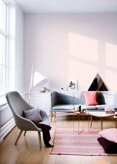 salon scandinave contemporain aménagé avec un canapé droit gris, un fauteuil gris, une table basse en cuivre et un tapis à rayures roses et grises