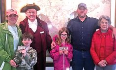"""The winners of the """"Chasing History Across Middlesex Scavenger Hunt"""" on March 18 pose in front of the Mitchell Map at the Urbanna Museum with colonial interpreter Paul Malone, who is wearing a tri-corner hat. From left they include the Deltaville family of Shannon Leonard, CJ Sears, Malone, Cheyenne Sears, Curtis Sears and Nancy Waldrop. They won $100.  by Tom Chillemi"""