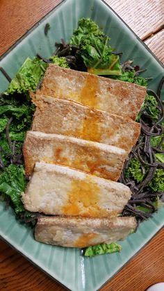 Black tofu on steamed kale and black bean noodles