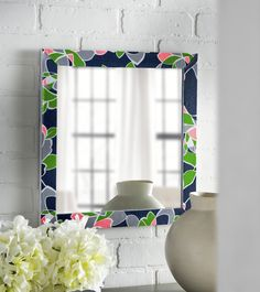 This easy DIY mirror was made with Mod Podge and fabric from a pillowcase - it's a great way to revamp an old piece or give a plain surface a bit of character.
