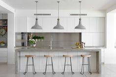 Weiße Küche mit grifflosen Fronten und Beton-Arbeitsplatte