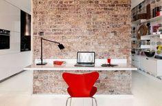 Style new-yorkais pour le bureau qui fait face à un mur de briques.