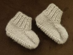 Chaussons gris bébé, tailles 0/3 ou 6 mois, tricotés aux aiguilles N°5. Tailles : a) 0/3 mois et b) 6 mois FOURNITURES : 1 paire d'aiguilles N°5 1 pelote de laine Julia de Zeeman 1 aiguille à laine pour faire les coutures. ECHANTILLON : 14 mailles et...