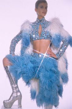 "Bob Mackie 1973 - Worn by Cher to ride an elephant for the Opening Night of Ringling Brothers and Barnum and Bailey Circus. Also worn on ""The Sonny and Cher Show"". A turquoise short midriff baring jacket with silver rim set mirrors and crystal stones with a white and turquoise ostrich feather cape. Together with matching ostrich feather pants and silver platform boots with crystal and turquoise stone encrusted platform heels."
