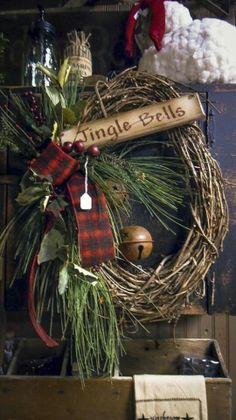 simple wreath w/ribbon , brass bell and a few sprigs of pine branches with wooden jingle bells sign