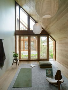 """A meditation room with a New Zealand wool rug, Japanese wooden blinds, a Sawkille stool, and Barber & OsgerbyHotaru Double Bubble Lights. """"I like the idea of repetition throughout the house,"""" Lockhart says. """"The same stools as bedside tables and side tables in the living room, the same rugs. For me, this adds to the serenity."""" Photograph by Mark Smith."""