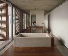 Vrijstaand betonnen bad in natte ruimte in open verbinding met de slaapkamer