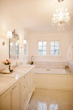 What an inviting space. This all white timeless master bathroom is so chic, yet so whimsical at the same time. And the combination of natural light with the wall scones and the chandelier over the soaking tub is perfect.