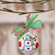 Ceramic ball ornament with bead and bow motif and festive motif.  Product: OrnamentConstruction Material: Cerami...