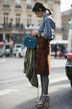 Blue shirt tucked into a brown corduroy narrow midi skirt, grey pantyhoses in snake print platform sandals. Carrying a small petrol blue handbag and a olive green parka over her arm to balance the outfit.