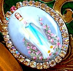 $89 Vintage porcelain cameo pendant locket featuring the Blessed Mother Virgin Mary as Our Lady of Lourdes of the Rosary standing in pink roses, hands folded in prayer. Golden AB rhinestones and 1 pink rhinestone accent. The vintage locket can hold 2 photo's and/or your prayer petition request to Our Lady.