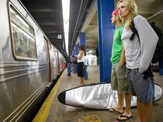 A couple waits for the subway at a New York City station after some early morning surfing at Far Rockaway Beach.