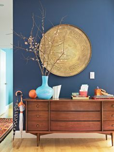 A dark accent wall draws your eye to a large exotic tray and other curiosities.
