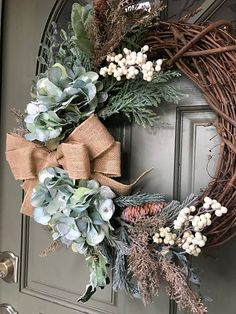 This beautiful holiday wreath featuring a beautiful muted blue colored hydrangea and golden branches with evergreens, metallic berries and pine cones is a great addition to your holiday and Christmas decor. A natural colored burlap bow completes the wreath. This wreath can be for