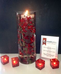 Submerged red orchids with floating candle, red votives + silver frames