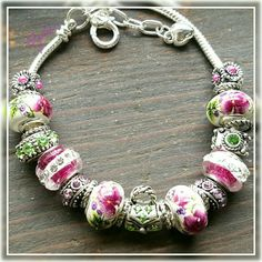 Floral country chic charm bracelet Stunning porcelain white glass beads w  burgundy Violet and green floral pattern, accented w only the finest stone and crystals on silver plated snake chain, can be moved onto a silver cuff or a stainless steel cuff. Lovely gift for someone special or treat yourself! Charms are compatible w all name brand charms and are of the same quality. Discounts given on bundles and to returning customers. Custom orders welcome. Salty Grace  Jewelry Bracelets