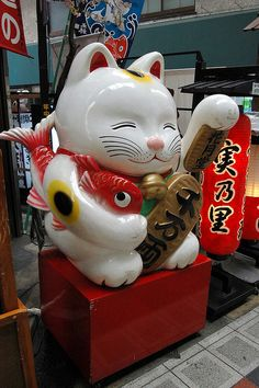 Maneki Neko   The Beckoning Cat: This well-known cat can be seen waving to you in businesses, restaurants and even on the streets. This cute cat is thought to have become popular in the beginning of the 20th century, and since then it has been bringing good luck and fortune to many. Traditionally, this purrbox is depicted as a calico japanese bobtail. Many things in pop-culture have been inspired by this, including Meowth from Pokémon.