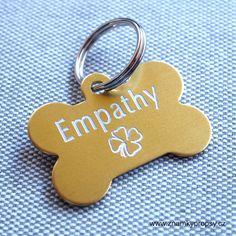 ID psí známka ve zlaté barvě s vyrytým textem na obou stranách psí známky.