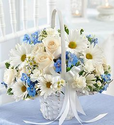 White roses, exquisite blue delphinium, white spray roses and more create this fun, fresh Flower Girl arrangement. It's beautifully hand-crafted in a classic white handled basket to coordinate perfectly with your wedding ensemble. $25.00