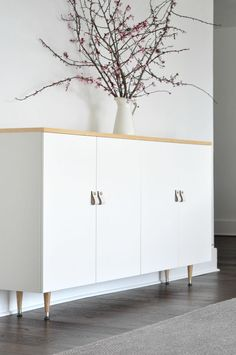 So worth it to add a bright white modern buffet/credenza to the dining room.  All it takes is a couple of cabinets, wood tapered legs, a wood top, and handles.  Easy and so functional!