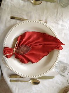 DIY Thanksgiving table setting with leaf napkins. (Fold napkin in half diagonally, accordion fold, fold in half again and pinch secure the bottom with twine.)