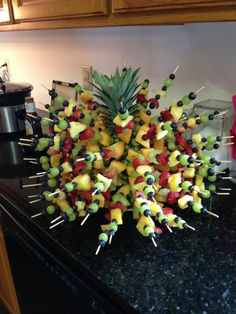 Whole pineapple with skewers of fruit. Saw this at another grad party. Decorative and fun way to serve fresh fruit