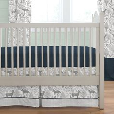 "Crib Dust Ruffle in Navy and Gray Woodland by Carousel Designs.  Think outside the box and get creative! Get your crib picture perfect with our box-pleat crib skirt including a 4-inch trim and accent. Finished length approximately 13-14 inches. Fits standard cribs using mattresses measuring approximately 28"" x 52"". Dry clean only."